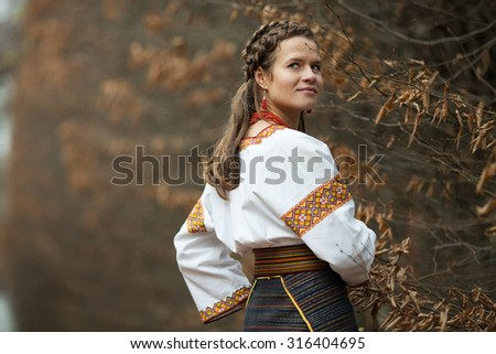 beautiful ukrainian bride in native embroidery suit on the background of trees in a autumn park