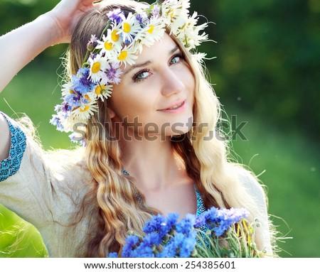 Beautiful ukrainian woman with flower wreath in fresh summer morning.  - stock photo