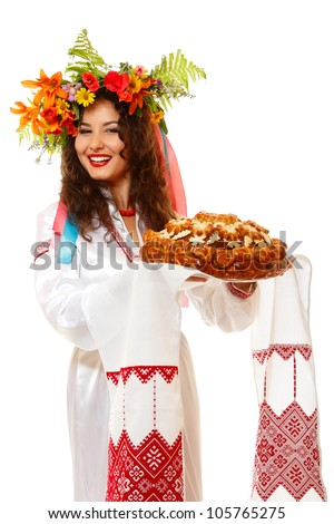 Beautiful ukrainian young hospitable woman in garland and native costume by tradition holding embroidered towel and round loaf, on white background - stock photo