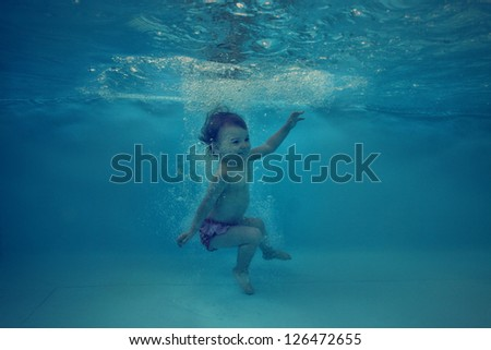 Beautiful underwater girl in the swimming pool - stock photo