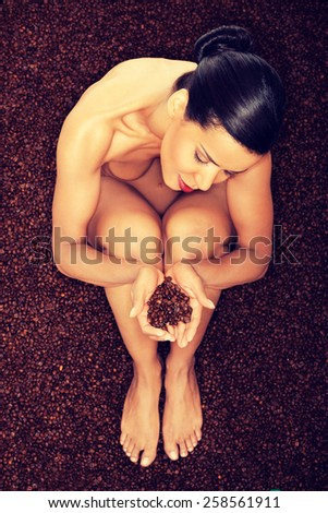 Beautiful undressed woman sitting in coffee beans. - stock photo