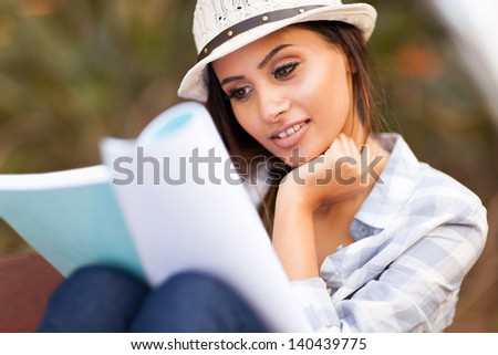 beautiful university student reading at the park - stock photo