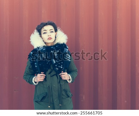 Beautiful unusual girl in green jacket on a red background. Close up, warm color - stock photo