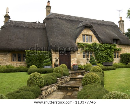 Beautiful upper class cottage with thatched roof and a pretty garden in the village of Chipping Campden, Cotswold, United Kingdom. - stock photo