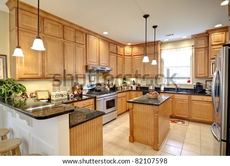 beautiful upscale kitchen with maple cabinets - stock photo