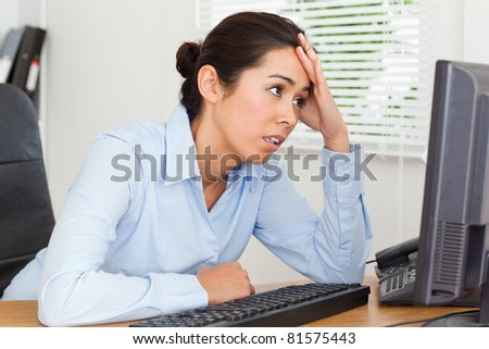 Beautiful upset woman looking at a computer screen while sitting at the office - stock photo