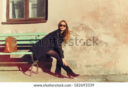 beautiful urban woman sitting on the bench in the city