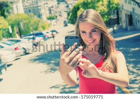 Beautiful urban woman taken picture of herself, selfie. Filtered image. - stock photo