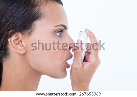 Beautiful using her inhaler on white background