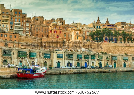 beautiful Valletta embankment with traditional colorful doors and anchored ship, Malta