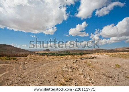 Beautiful valley in the Middle East with low mountains and small town in the distance under the white clouds on a sunny day  - stock photo