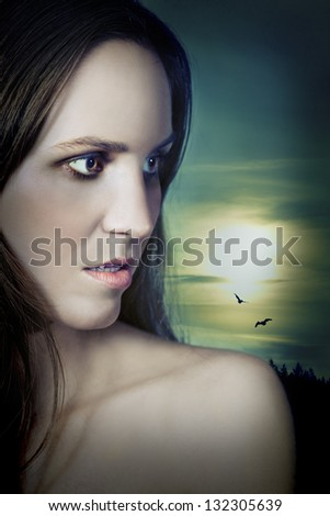 Beautiful vampire girl under the moon in profile looking to the side. Novel cover look. - stock photo