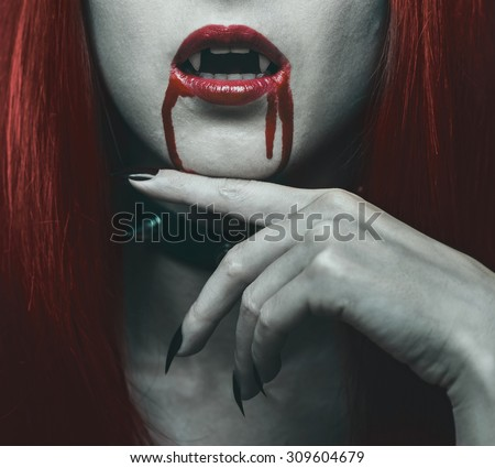 Beautiful vampire woman, close-up red lips in blood. Halloween or horror theme - stock photo