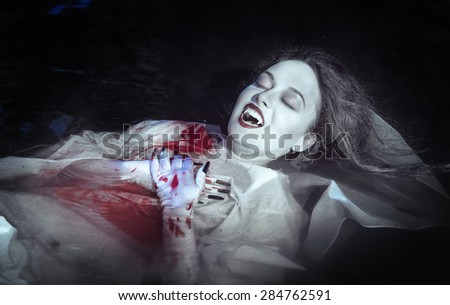 Beautiful vampire woman dressed white bloody shirt lying in the river