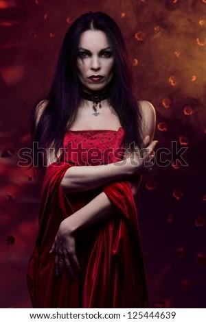 Beautiful vampire woman in red dress - stock photo