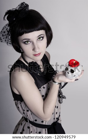 Beautiful vampire woman with green eyes and a skull in her hands - stock photo