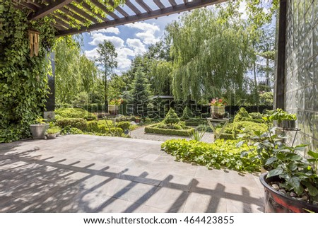 Beautiful vast garden in Japanese style seen from a shaded veranda