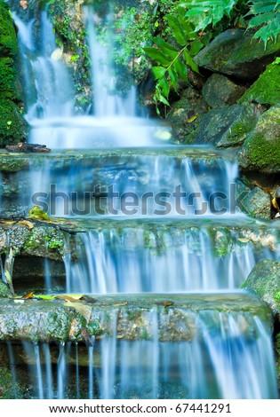Beautiful veil cascading waterfalls, mossy rocks - stock photo