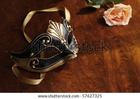 Beautiful Venetian mask in black and gold with a rose next to it.