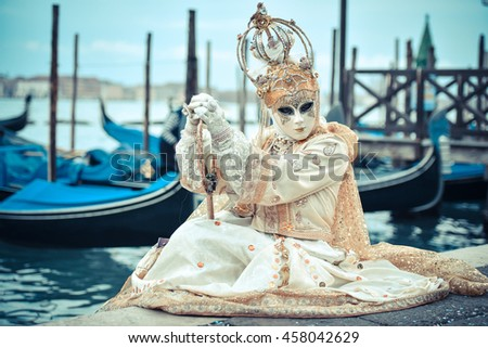 Beautiful Venetian masked model from the Venice Carnival 2015 with Gondolas in the background. Venice mask near San Marco Plaza. - stock photo