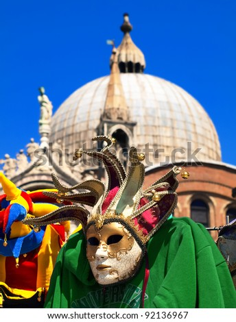 Beautiful Venice city scene at Piazza San Marco with Venetian carnival mask and famous Palazzo Ducale in the background, Italy - stock photo
