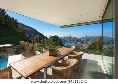 beautiful veranda with wooden table and wicker chairs, 