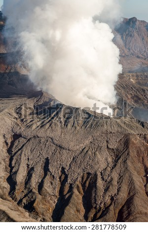 Beautiful Vertical Aerial View Smoke Gas Steam Crater of Mount Aso Volcano Caldera largest active Volcano in Japan Island eruption under Sunny Clear Blue Sky in Summer Daytime, Kumamoto, Kyushu - stock photo