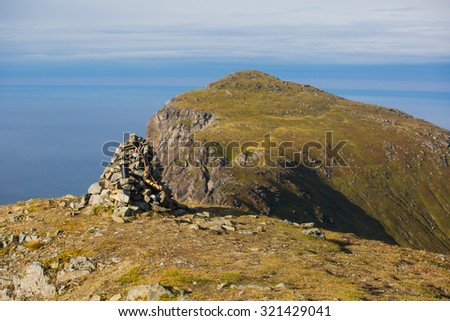 Beautiful Vibrant Norwegian Mountain Landscape from Ryten peak - famous mountain in Lofoten Islands, Moskenes municipality, Nordland with a view of Kvalvika beach, with hiking tourists and blue sky - stock photo