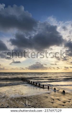 Beautiful vibrant seascape at sunset image with dramatic sky - stock photo