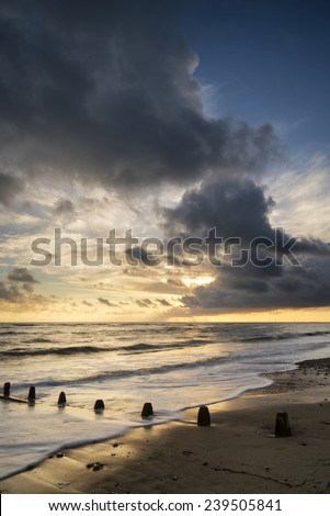 Beautiful vibrant seascape at sunset image with dramatic sky