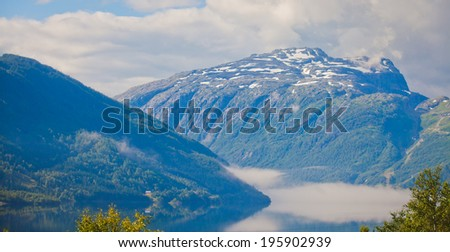 Beautiful vibrant summer norwegian landscape with atlantic road, fjord, mountain, lake, trees and blue sky, Norway - stock photo