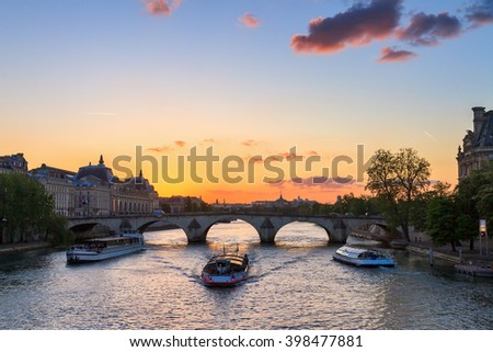 Beautiful vibrant sunset over the river Seine in Paris, France, with tourist canalboats - stock photo