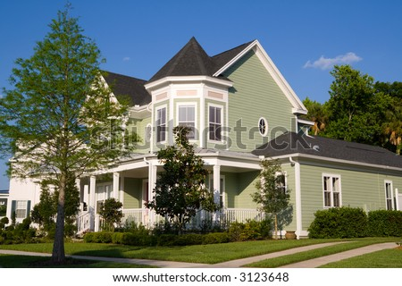 beautiful Victorian-styled home with lush landscaping - stock photo