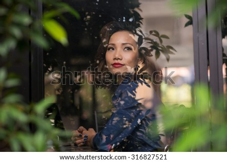 Beautiful Vietnamese business woman sitting in a cafe and looking through the window
