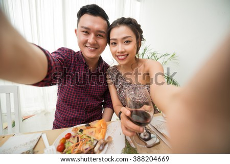 Beautiful Vietnamese couple taking selfie at party table