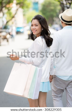 Beautiful Vietnamese woman walking outdoors with her boyfriend, view from the back - stock photo