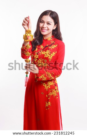 Beautiful Vietnamese woman with red ao dai holding lucky decorate object for celebrate lunar new year on white background - stock photo
