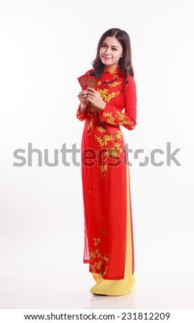 Beautiful Vietnamese woman with red ao dai holding lucky red packet for celebrate lunar new year on white background - stock photo