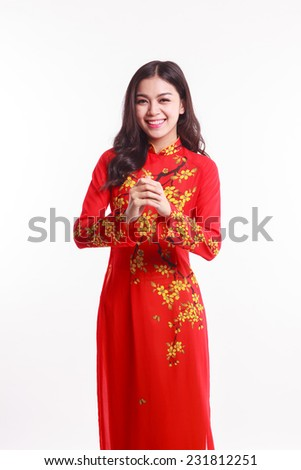 Beautiful Vietnamese woman with red ao dai show the hand for celebrate lunar new year on white background - stock photo