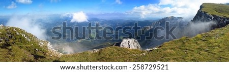 beautiful view down the mountain. Traveling clouds in the horizon - stock photo