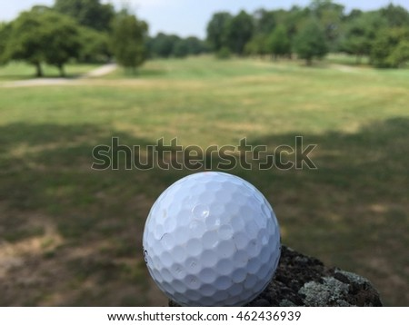 Beautiful view of a golf course will a ball sitting in the foreground before tee off.