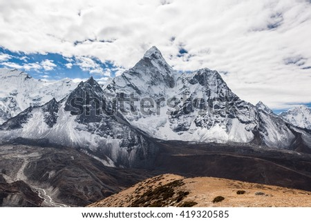 Beautiful view of Ama Dablam mountain summit on the famous Everest Base Camp trek in Himalayas, Nepal. Snowy mountain summit on a cloudy day. Panoramic mountain summit landscape. - stock photo