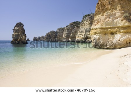 Beautiful view of an idyllic wild beach in summertime - sand and sea at Algarve, Portugal coast. - stock photo