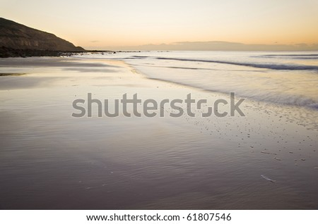Beautiful view of beach at sunrise with rock details - stock photo