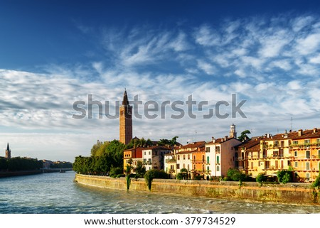Beautiful view of colorful facades of old houses on waterfront of the Adige River and bell tower of Santa Anastasia church in Verona, Italy. Verona is a popular tourist destination of Europe. - stock photo