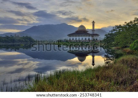 Beautiful view of Darul Quran Mosque with reflections during sunrise (soft focus, shallow DOF, slight motion blur) - stock photo