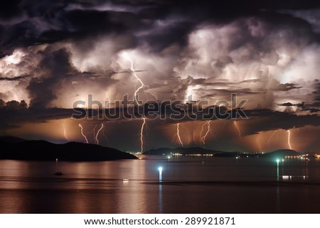 Beautiful view of dramatic dark stormy sky and lightning over Nha Trang Bay of South China Sea in Khanh Hoa province at night in Vietnam. Nha Trang city is a popular tourist destination of Asia. - stock photo