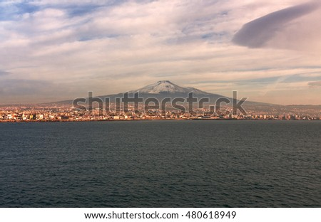 Beautiful view of Etna volcano and the city of Catania in Sicily, Italy at sunrise. Mediterranean Sea  on foreground.