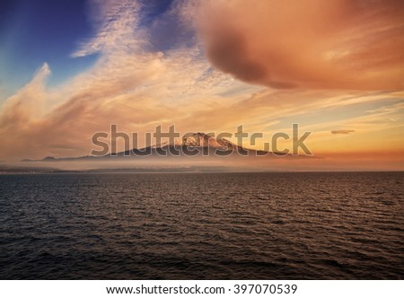 Beautiful view of Etna Volcano in Sicily at sunset with sea on foreground - stock photo