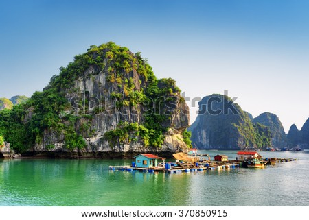 Beautiful view of floating fishing village in the Halong Bay (Descending Dragon Bay) at the Gulf of Tonkin of the South China Sea, Vietnam. Landscape formed by karst towers-isles in various sizes.